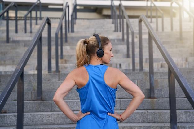 Achteraanzicht van een sportvrouw in een koptelefoon die wegkijkt terwijl ze met de handen op de taille buiten klaar staat