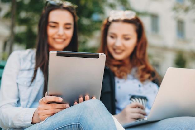 Achteraanzicht van een tablet die wordt gebruikt door twee mooie meisjes die zittend op een bankje buiten in het park glimlachen.