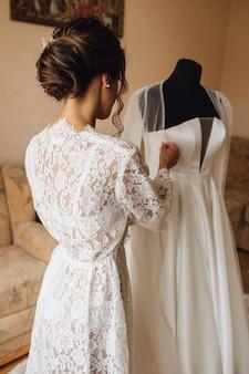Achteraanzicht van een tedere bruid in de huwelijksochtend bereidt zich voor op de huwelijksceremonie
