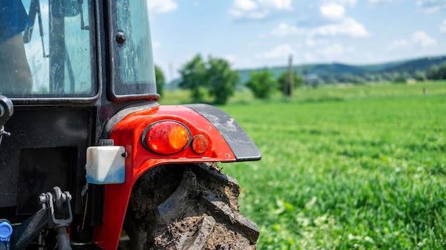 Achteraanzicht van een tractor met groen veld op de achtergrond