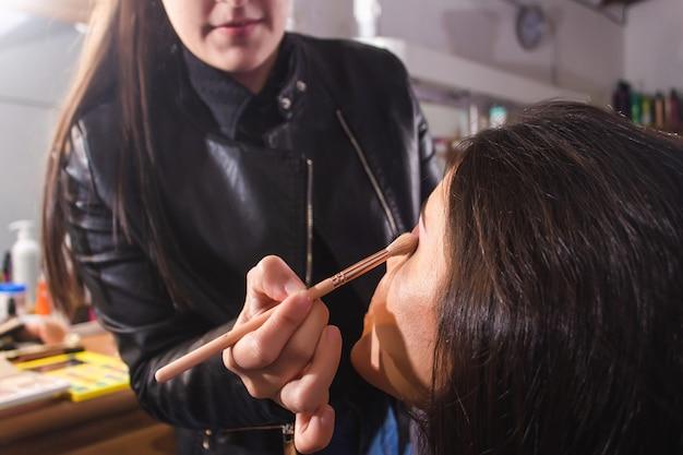 Achteraanzicht van een visagist die de oogcontour van een mooi jong meisje in de schoonheidssalon vervaagt.