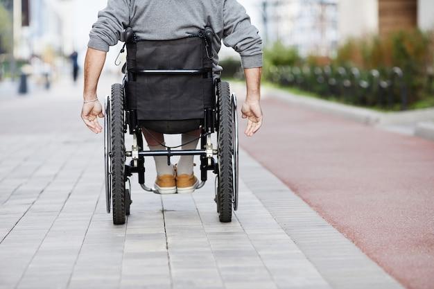 Achteraanzicht van een volwassen man die in een rolstoel langs de straat rijdt