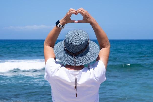 Achteraanzicht van een volwassen vrouw met een blauwe hoed die naar de horizon kijkt boven water en een hartvorm maakt met de handen