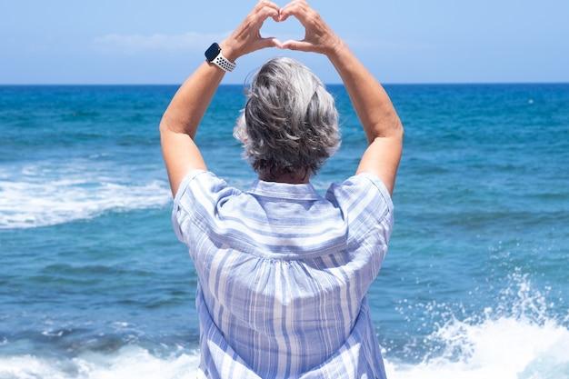 Achteraanzicht van een volwassen vrouw met een blauwe hoed die naar de horizon over water kijkt en een hartvorm maakt met de handen. concept van liefde en vrijheid
