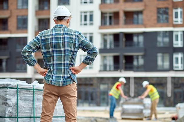 Achteraanzicht van een voorman in een veiligheidshelm die met zijn handen op zijn heupen op de bouwplaats staat