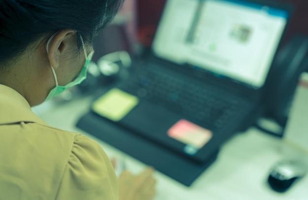 Achteraanzicht van een vrouw die een gezichtsmasker draagt dat aan een bureau werkt met een laptop op kantoor aziatische vrouwelijke werknemer