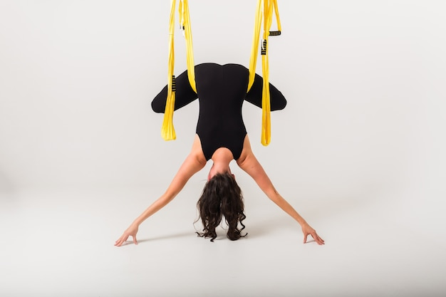 Achteraanzicht van een vrouw die een omgekeerde anti-zwaartekracht yoga pose uitvoert in een hangmat op een witte muur