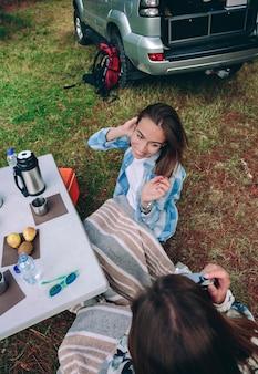 Achteraanzicht van een vrouw die foto's maakt naar een gelukkige jonge vriend terwijl ze aan het ontbijten is op de camping