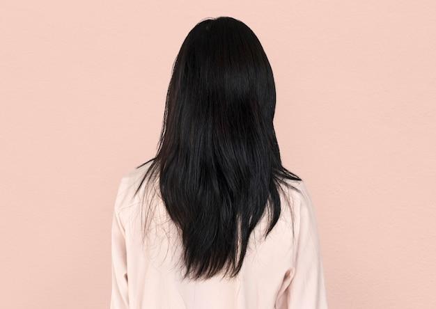 Achteraanzicht van een vrouw die haar lang zwart haar laat zien
