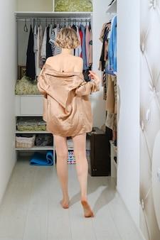 Achteraanzicht van een vrouw die naar de kleedkamer gaat en haar pyjama uittrekt