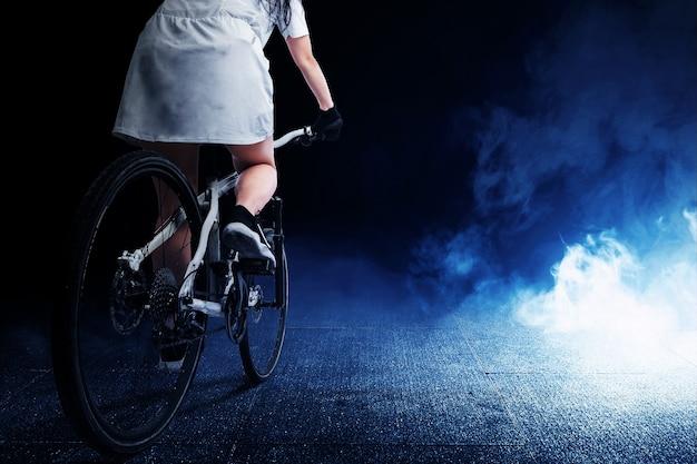 Achteraanzicht van een vrouw die op een fiets rijdt met een lichte achtergrond
