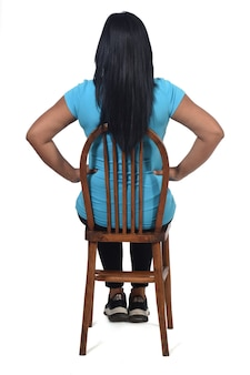 Achteraanzicht van een vrouw die op haar rug zit met een witte achtergrond