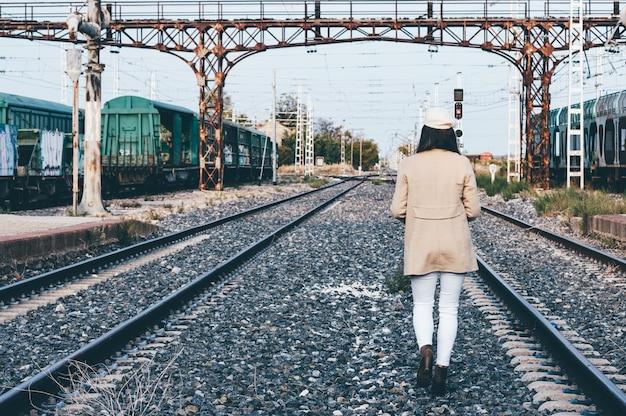 Achteraanzicht van een vrouw gekleed met een baret en een beige jas die over een spoorweg loopt.