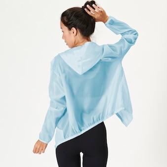 Achteraanzicht van een vrouw in een babyblauw sportjasje