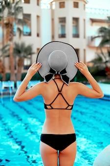 Achteraanzicht van een vrouw in een bikini en een modieuze hoed die in het zwembad staat