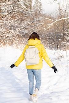 Achteraanzicht van een vrouw in een felgele jas en spijkerbroek met een rugzak in een besneeuwd landschap bos loopt door de sneeuwlaag