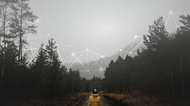 Achteraanzicht van een vrouw in een gele windjack die zich in een mistig bos bevindt