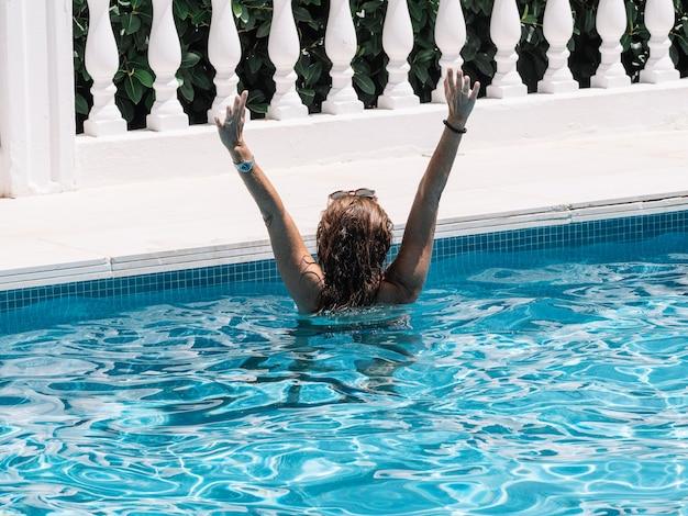 Achteraanzicht van een vrouw in een zwembad tijdens een zonnige zomerdag