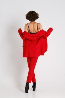 Achteraanzicht van een vrouw in rode pantsui en paaldanslaarzen die in de studio lopen