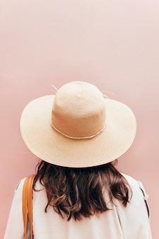Achteraanzicht van een vrouw met bruin haar in een geweven hoed