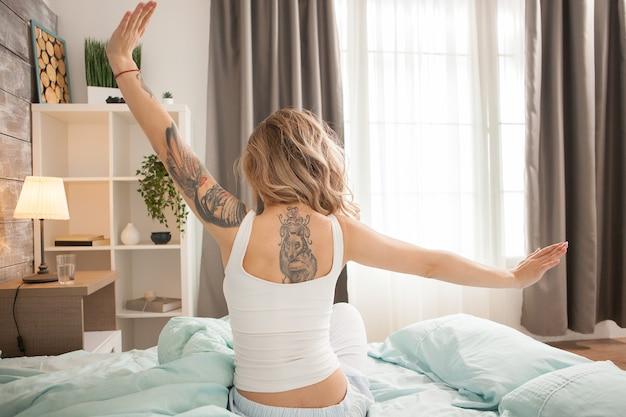 Achteraanzicht van een vrouw met een tatoeage op haar rug die zich 's ochtends uitstrekt.