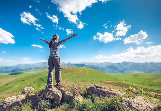 Achteraanzicht van een vrouw met opgeheven handen op de achtergrond van groene heuvels en blauwe lucht met wolken verkennen