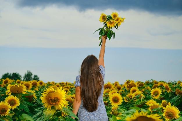 Achteraanzicht van een vrouw met zonnebloemen boeket. jonge vrouw met zonnebloemen in de hand die uit de lucht reikt
