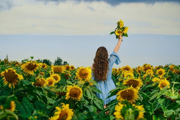 Achteraanzicht van een vrouw met zonnebloemenboeket in de hand