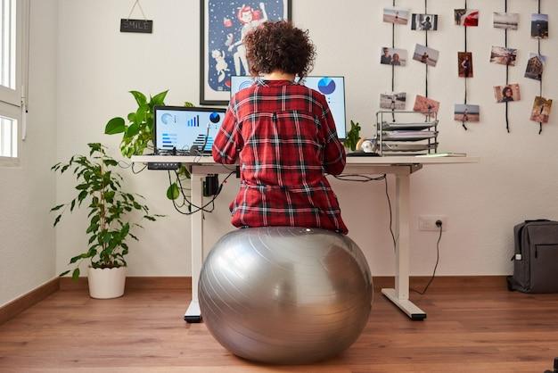 Achteraanzicht van een vrouw telewerken zittend op een fitball voor haar bureau