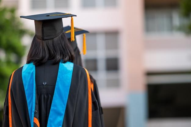 Achteraanzicht van een vrouwelijke afgestudeerde met een universitair diploma