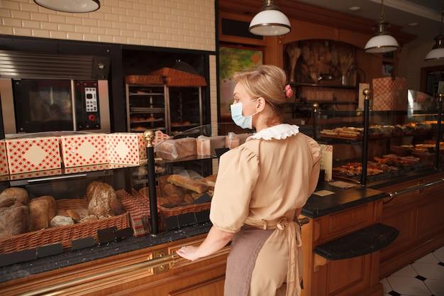 Achteraanzicht van een vrouwelijke bakker die een medisch masker draagt in haar bakkerijwinkel