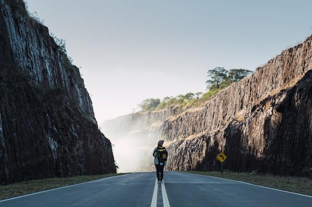 Achteraanzicht van een vrouwelijke reiziger in vrijetijdskleding met rugzak die op de asfaltweg loopt.