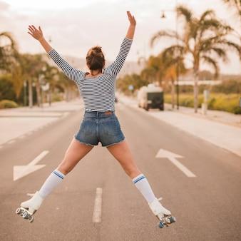 Achteraanzicht van een vrouwelijke skater met haar benen uit elkaar en opgeheven armen springen op de weg