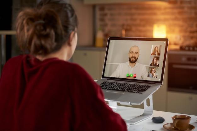 Achteraanzicht van een vrouwelijke werknemer die op afstand werkt in gesprek met haar collega over zaken in een videoconferentie op een laptop thuis.