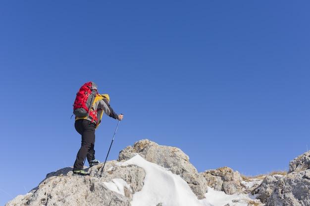 Achteraanzicht van een wandelaar die naar het uitzicht kijkt vanaf een besneeuwde bergtop