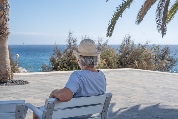 Achteraanzicht van een witharige senior man buiten aan de zee, zittend in de schaduw van een boom