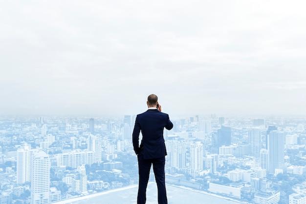Achteraanzicht van een zakenman praten aan de telefoon bovenop het gebouw