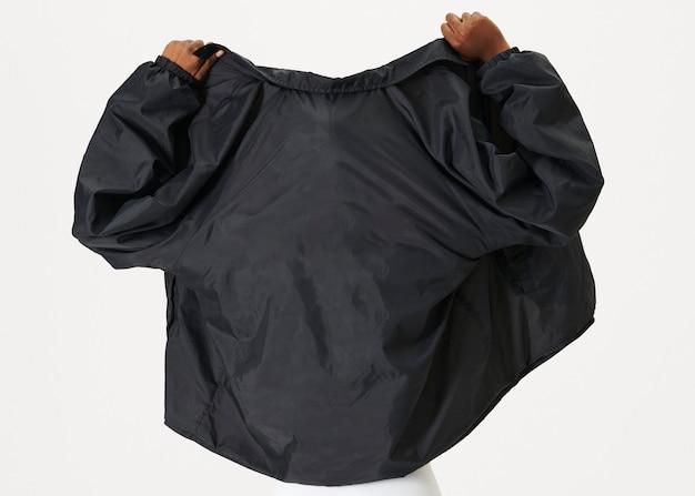 Achteraanzicht van een zwarte vrouw die een zwarte jas draagt