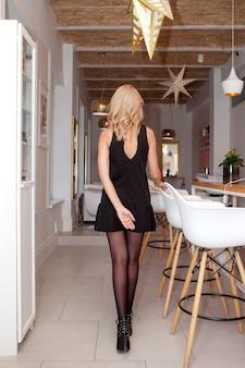 Achteraanzicht van elegant geklede jonge vrouw in schoonheidssalon interieur; achteraanzicht van slanke zakelijke vrouw op hoge hakken staan