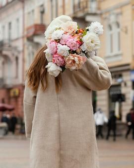 Achteraanzicht van elegante vrouw buitenshuis boeket bloemen te houden in de lente