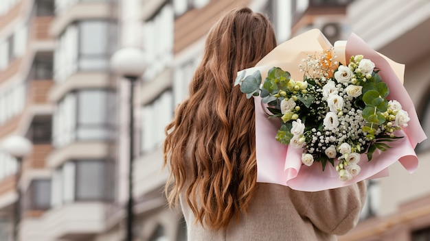 Achteraanzicht van elegante vrouw met boeket bloemen buitenshuis