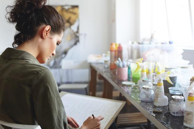 Achteraanzicht van ernstig geconcentreerde jonge europese vrouwelijke ontwerper met donker haar, bezig met nieuwe collectie sieraden of kleding in haar lichte ruime werkplaats, met een inspirerend gevoel. creatieproces