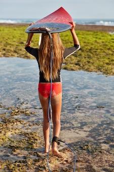 Achteraanzicht van ervaren vrouwelijke surfer draagt surfplank boven het hoofd, wordt vastgemaakt met legrope