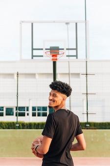 Achteraanzicht van etnische vrolijke jongeman op basketbalveld