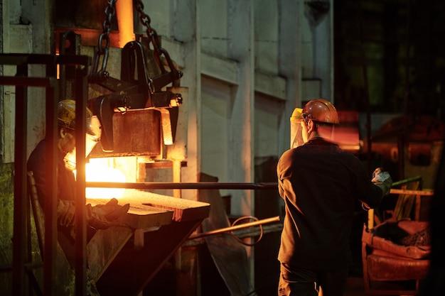 Achteraanzicht van fabrieksman in helm met ijzeren stok tijdens het werken met ovens in de industrie