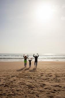 Achteraanzicht van familie met surfplanken boven hun hoofd