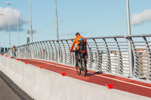 Achteraanzicht van fietser met kinderstoel en baby. familie fietsen in de stad op de brug. vader met kind paardrijden fiets buitenshuis. actieve sport vrije tijd.
