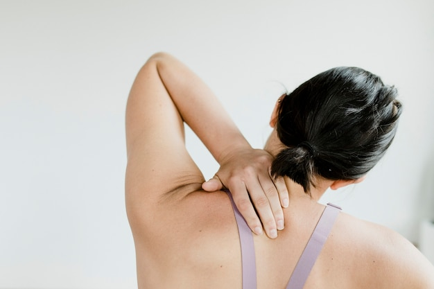 Achteraanzicht van fitnessvrouw die haar rug bereikt