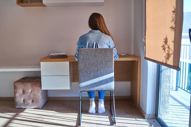 Achteraanzicht van freelancer-meisje tijdens online werken op afstand op de werkplek thuiskantoor