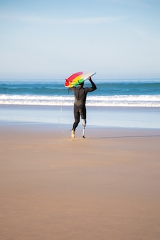 Achteraanzicht van gehandicapte surfer naar zee met bord. actieve man met geamputeerde been surfplank houden en surfen op zomervakantie